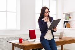 Бизнес-леди писать вниз примечания на офисе Стоковые Фото