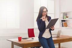 Бизнес-леди писать вниз примечания на офисе Стоковое Изображение