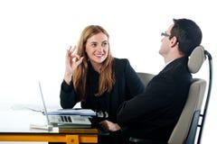 Бизнес-леди показывать О'КЕЫ к коллеге на работе Стоковые Изображения RF