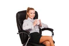 Бизнес-леди при чашка сидя в стуле Стоковые Изображения