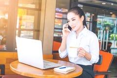 Бизнес-леди работают на компьютере и контактируют чернь Стоковое Фото