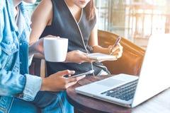 Бизнес-леди работают на компьютере и принимают примечания в тетради Стоковые Изображения
