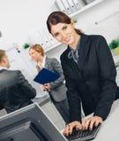 Бизнес-леди работая на компьютере в офисе Стоковые Изображения RF