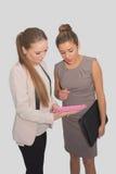2 бизнес-леди работая на розовой таблетке Стоковая Фотография