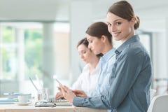 Бизнес-леди работая на столе офиса с ее коллегами Стоковое Изображение