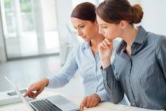 Бизнес-леди работая совместно на компьтер-книжке Стоковая Фотография