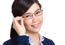 Бизнес-леди регулирует стекла стоковые изображения