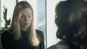 2 бизнес-леди рядом с окном в зале обсуждают темы сток-видео