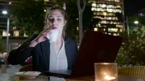Бизнес-леди сидя в кафе на ноче, работая на портативном компьютере и звоня телефонные звонки видеоматериал