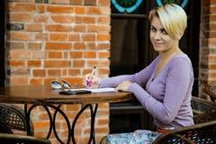Бизнес-леди сидя в кафе на таблице стоковое фото