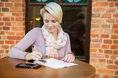 Бизнес-леди сидя в кафе на таблице Стоковые Изображения