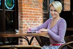 Бизнес-леди сидя в кафе на таблице стоковое изображение rf