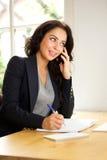 Бизнес-леди сидя в офисе говоря на телефоне Стоковое фото RF