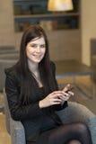 Бизнес-леди сидя в офисе с телефоном Стоковые Изображения RF