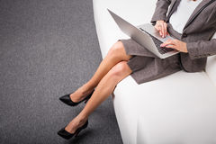 Бизнес-леди сидя на софе с компьютером в ее подоле Стоковое Изображение