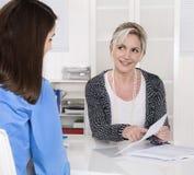 Бизнес-леди 2 сидя на столе в встрече стоковое изображение