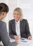 Бизнес-леди 2 сидя на столе: говорить клиента и советника стоковая фотография rf