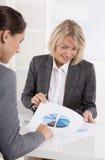 Бизнес-леди 2 сидя на столе: говорить клиента и советника стоковые изображения rf