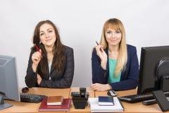 2 бизнес-леди сидя на столе, ручке удерживания в руке и взгляде к рамке Стоковое Изображение RF