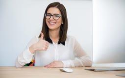 Бизнес-леди сидя на таблице с большим пальцем руки вверх Стоковое фото RF