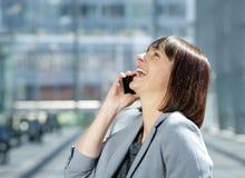 Бизнес-леди смеясь над и говоря на сотовом телефоне Стоковое Изображение