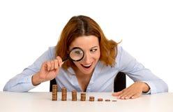 Бизнес-леди смотря растущий стог монеток через лупу Стоковые Фото