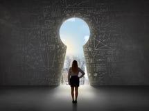Бизнес-леди смотря keyhole с яркой концепцией городского пейзажа Стоковая Фотография RF