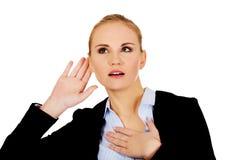 Бизнес-леди сотрясенная детенышами подслушивает переговор стоковые изображения