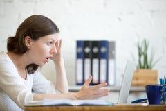 Бизнес-леди сотрясенная детенышами смотря портативный компьютер стоковое изображение rf