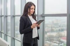 Бизнес-леди стоя на окне с таблеткой Стоковая Фотография