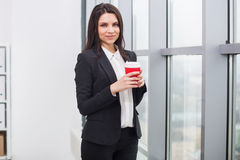 Бизнес-леди стоя на окне с чашкой Стоковые Фото