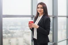 Бизнес-леди стоя на окне с чашкой Стоковая Фотография RF