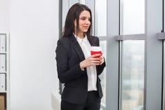 Бизнес-леди стоя на окне с чашкой Стоковые Изображения