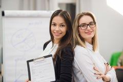 2 бизнес-леди стоя на офисе перед диаграммой сальто Стоковая Фотография RF
