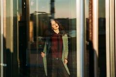 Бизнес-леди стоя самостоятельно рядом с большим офисом окон Стоковая Фотография RF