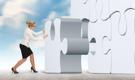 Бизнес-леди с белой головоломкой на предпосылке неба Стоковое фото RF