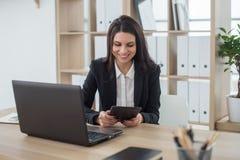 Бизнес-леди с тетрадью в офисе, рабочем месте Стоковые Фото