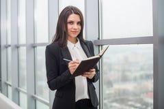 Бизнес-леди с тетрадью окно в офисе Стоковое фото RF