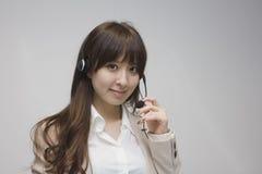 Бизнес-леди усмехаясь с шлемофоном Стоковое Изображение