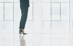 Бизнес-леди фото крупного плана нося современный костюм Офис просторной квартиры открытого пространства Панорамная предпосылка ок Стоковое Изображение RF