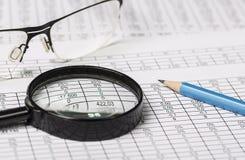 Бизнес-исследование Крупный план зрелищ лупы и карандаша на бумаге с числами Стоковые Изображения