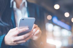 Бизнес-леди вручают используют сотовые телефоны в офисе стоковая фотография rf