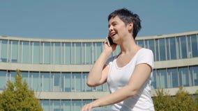 Бизнес-леди в белой футболке сидя перед офисным зданием и говоря на телефоне видеоматериал
