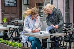 2 бизнес-леди в внешнем кафе закрыли дело и знак t Стоковое Изображение RF