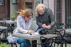 2 бизнес-леди в внешнем кафе закрыли дело и знак t Стоковое Изображение