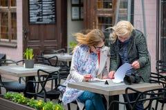 2 бизнес-леди в внешнем кафе закрыли дело и знак t Стоковая Фотография RF