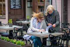 2 бизнес-леди в внешнем кафе закрыли дело и знак t Стоковые Фотографии RF