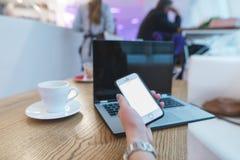 Бизнес-леди в кафе с телефоном в руке против предпосылки компьтер-книжки и кофе Конец-вверх рук Стоковые Изображения
