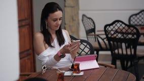 Бизнес-леди в кафе улицы выпивая турецкий чай и пользы smartphone акции видеоматериалы