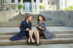 2 бизнес-леди в пальто обсуждают на предпосылке  Стоковые Изображения